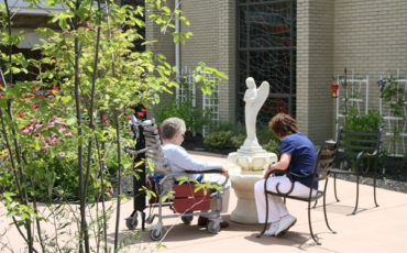 Elders and family members love to sit by the fountain within the Sensory Garden