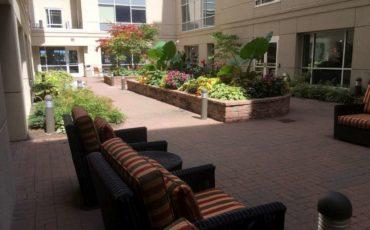 A comfortable chair invites residents into the Atrium Courtyard Garden